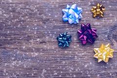 Bögen für Geschenke auf einer Holzoberfläche mit Schneeflocken Weihnachtshintergrund mit mehrfarbigen Bögen Stockfotos