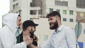 Bögen gav fem till en vännärbild Vuxna unga grabbar skrattar closeupen stock video