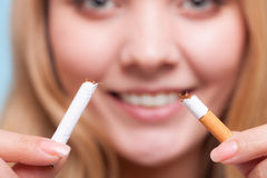Böjelse. Flicka som bryter cigaretten. Avslutat röka. arkivfoto