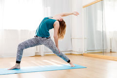 Böjlig slank flicka som gör hög utfallövning i yogagrupp arkivbilder