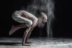 Böjlig yogaman som gör brahmachariasana för handjämviktsasana fotografering för bildbyråer