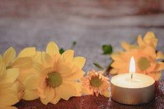 Bön- och hoppbegrepp Retro stearinljusljus och den gula blomman med belysningeffekt och blänker abstrakt bakgrund med bokehdefo royaltyfria bilder