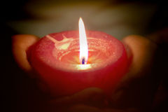 Bön- och hoppbegreppet av stearinljuset tänder i händer royaltyfria foton