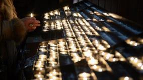 Bön som tänder offer- stearinljus Brännande minnes- stearinljus i katolska kyrkan Midnatt mass för jul fira stock video