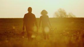 Bönder - en man och en kvinna som går över fältet på solnedgången Bär en trädplanta, kan bevattna och en skyffel