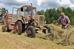 Bönder sätter in, agronomtraktor-chauffören på arbete som kontrollerar nya mummel Arkivbilder