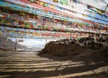 Bönen sjunker att spänna över en väg på ett bergpasserande, Tibet Fotografering för Bildbyråer