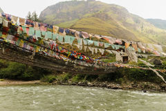 Bönen sjunker på järnbron av den Tamchog Lhakhang kloster, den Paro floden, Bhutan Fotografering för Bildbyråer