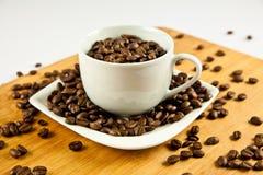 Bönor av kaffe och koppen på plattan Arkivfoto