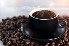 Bönor för en kopp kaffe på kornen av kaffe i strålarna av ljus Slapp fokus Frigör stället för inskrifter överst Royaltyfria Bilder