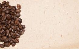 Bönor för ett handfullkaffe på en beige bakgrund royaltyfria bilder