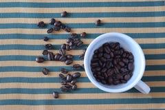 Bönor för svart kaffe i den vita koppen på härligt tyg Royaltyfri Fotografi