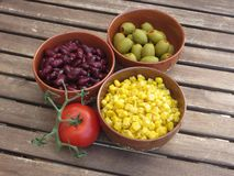 Bönor konserverar, och oliv i röd terrakotta bowlar arkivbild