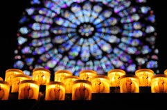 Bönstearinljus med det rose fönstret i Notre Dame, Pa Royaltyfria Bilder