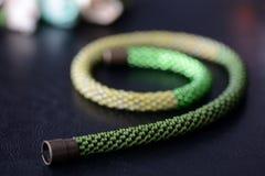 Bördeln Sie grüne Abstufungen der Häkelarbeithalskette drei auf einem dunklen Hintergrund Lizenzfreies Stockfoto
