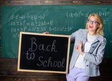 Början av den nya skolasäsongen Kvinnaläraren rymmer svart tavlainskriften tillbaka till skolan Är du ordnar till för att studera royaltyfri fotografi