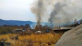 Början av en stor brand i aftonen i byn arkivfoto