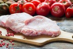 Början för stödfläskkotlettkött klippte med tomater på skärbräda Fotografering för Bildbyråer