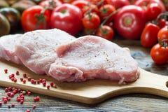 Början för stödfläskkotlettkött klippte med tomater på skärbräda Arkivfoto
