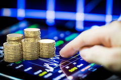 Börse, die mit digitaler Tablette und Stapel der Goldmünze aufpasst stockbild