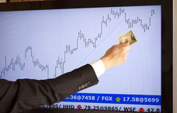 Börsenmakler, der Zustimmung mit einem Dollar in der Hand gibt Stockbild