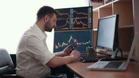 Börsmäklaren i den vita skjortan arbetar i ett övervaka rum med skärmskärmar Finans för börshandelForex lager videofilmer