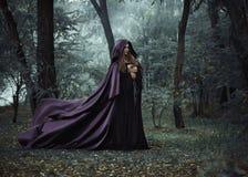 Böse Hexe in einem langen dunklen Mantel, der in Holz wandert Stockfoto