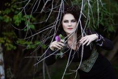 Böse Hexe versteckt sich hinter den Büschen Stockfoto