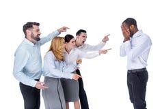 Böse Kollegen, die an ihrem Mitarbeiter verspotten stockfotografie