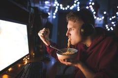 Böses jugendlich spielt Videospiele auf einem Computer und isst Schnellimbiß Abendessen am Computer nachts stockfotografie