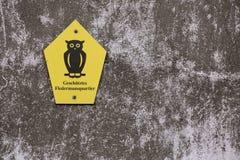 Búho alemán oficial que marca un área de protección de la naturaleza El hogar protegido medios del palo del texto fotos de archivo
