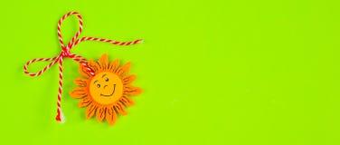 Búlgaro Martenitsa y sol en fondo verde imágenes de archivo libres de regalías