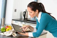 Búsqueda de la cocina de la tablilla de la receta de la lectura de la mujer joven Imagen de archivo