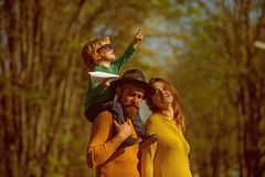 Búsqueda de la familia para la fuente de inspiración Madre y padre que llevan a cuestas al pequeño hijo que juega con el avión de fotografía de archivo libre de regalías