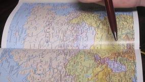 Búsqueda de la mano del hombre adecuado que varios lugares en la geografía de papel trazan por una pluma Cierre para arriba metrajes