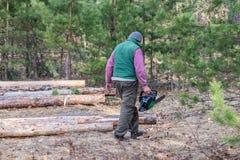 Bûcheron avec une tronçonneuse à disposition dans la forêt photos stock