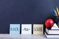 Bücher, Apfel, Bleistifte und ein Papierflugzeug Auf einem dunklen Hintergrund mit der Aufschrift zurück zu Schule Stockfotografie