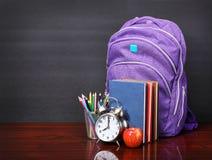 Bücher, Apfel, Rucksack, Wecker und Bleistifte auf hölzernem Schreibtisch Lizenzfreies Stockfoto