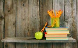 Bücher, Apfel und Bleistifte auf einem hölzernen Regal Lizenzfreies Stockfoto