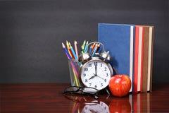Bücher, Apfel, Wecker und Bleistifte auf hölzerner Schreibtischtabelle Lizenzfreie Stockbilder
