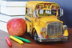 Bücher, Apfel, Zeichenstifte und Studentenbus Lizenzfreie Stockbilder