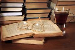 Bücher auf dem Tisch, Gläser und eine Schale Stockbild