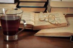 Bücher auf dem Tisch, Gläser und eine Schale Stockfotografie