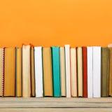 Bücher auf Schmutzholztisch-Schreibtischregal in der Bibliothek Zurück zu Schulhintergrund mit Kopienraum für Ihren Anzeigentext  Lizenzfreie Stockfotografie