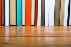 Bücher auf Schmutzholztisch-Schreibtischregal in der Bibliothek Zurück zu Schulhintergrund mit Kopienraum für Ihren Anzeigentext  Lizenzfreies Stockbild