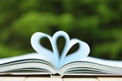 Bücher auf Tabelle mit der Spitze eine geöffnet und den Seiten, die Herz bilden Stockfotos