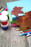 Bücher, Bleistifte und Ahornblatt Stockbilder