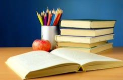 Bücher, Bleistifte und Apfel auf der Tabelle Stockfotografie
