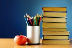 Bücher, Bleistifte und Apfel auf der Tabelle Lizenzfreies Stockbild