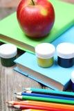 Bücher, Bleistifte und ein Apfel Stockfotografie